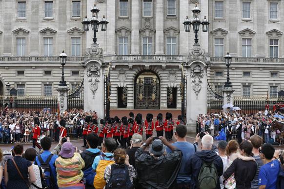 लंदन में रॉयल बेबी के जन्म के बाद बकिंघम पैलेस के बाहर गॉर्ड के बदलाव को देखते हुए लोग।