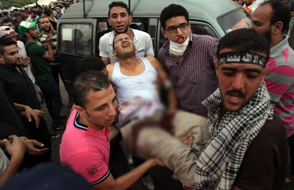 मिस्र के नस्र शहर में एक घायल व्यक्ति को अस्पताल ले जाते अपदस्थ राष्ट्रपति मोहम्मद मोरसी के समर्थक।