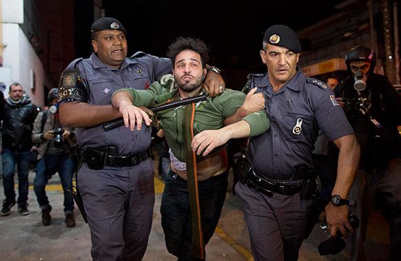 ब्राजील में सरकार के खिलाफ नारेबाजी कर रहे एक प्रदर्शनकारी को गिरफ्तार कर ले जाते पुलिसकर्मी।