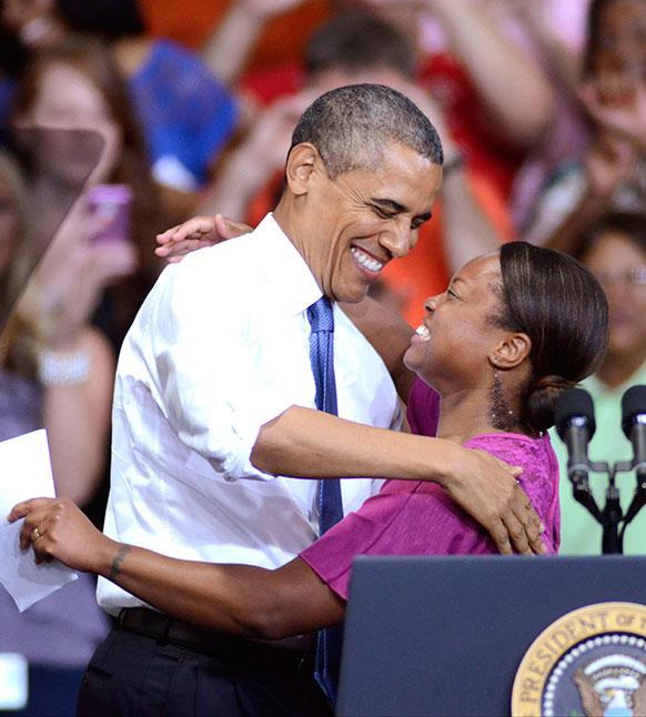 तेन में अमेरिकी राष्ट्रपति बराक ओबामा एक कर्मचारी से गले मिलते हुए।
