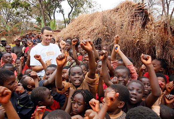 तंजानिया के शरणार्थी कैंप में बच्चों के लिए NBA के फुटबॉलर स्टीफेन केरी राहत सामग्री के साथ।