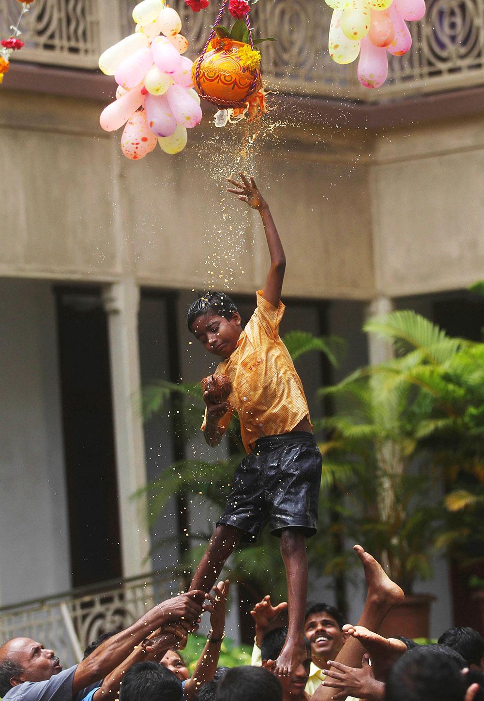 अहमदाबाद में दही हांडी फोड़ता एक बच्चा।