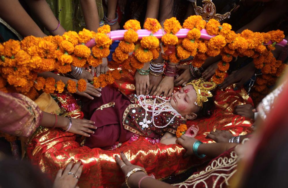 एक बच्चे को पालने में सुलाकर भगवान श्रीकृष्ण जन्माष्टमी का उत्सव मनाती कुछ महिलाएं।