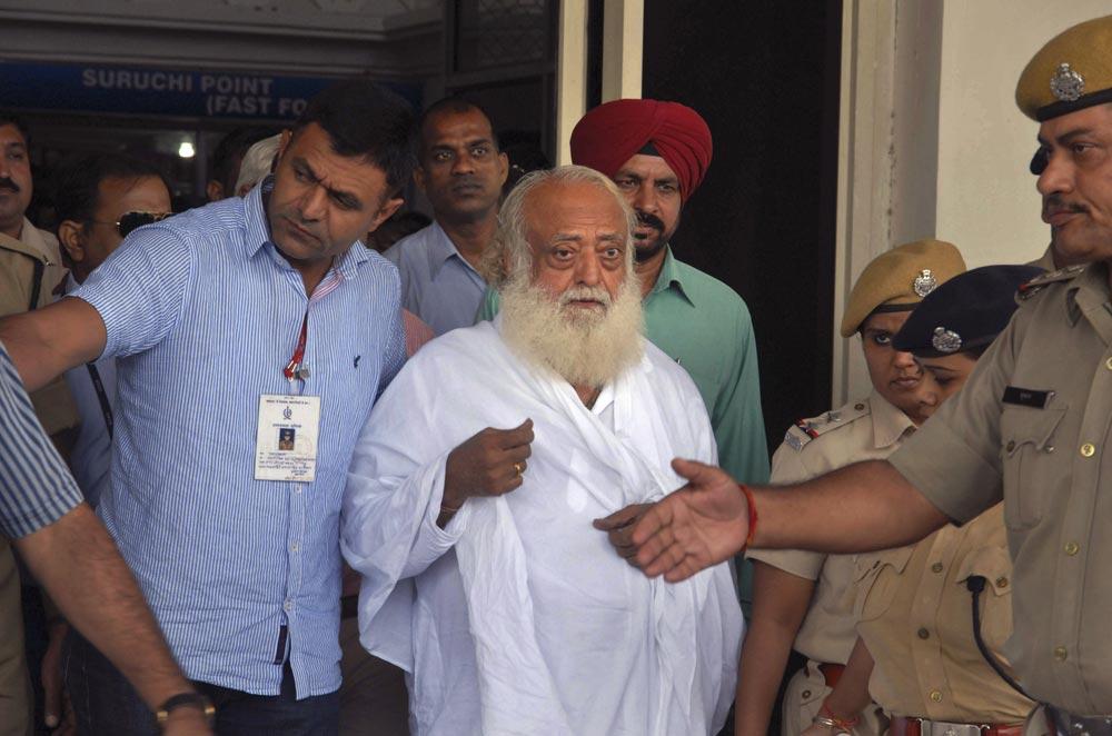 नाबालिग यौन शोषण केस में गिरफ्तारी के बाद आसाराम को जोधपुर हवाईअड्डे से बाहर लेकर आती पुलिस।