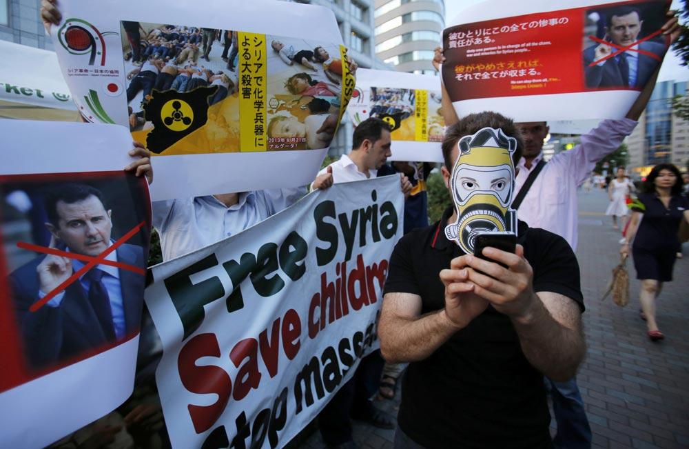 टोक्यो में सीरियाई राष्ट्रपति बशर अल असद के खिलाफ प्रदर्शन करते लोग।