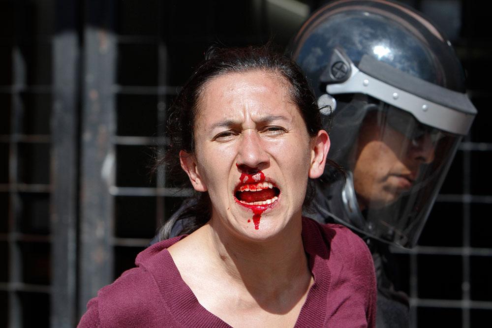 मेक्सिको सिटी में मार्च के दौरान घायल प्रदर्शनकारी को ले जाती पुलिस।