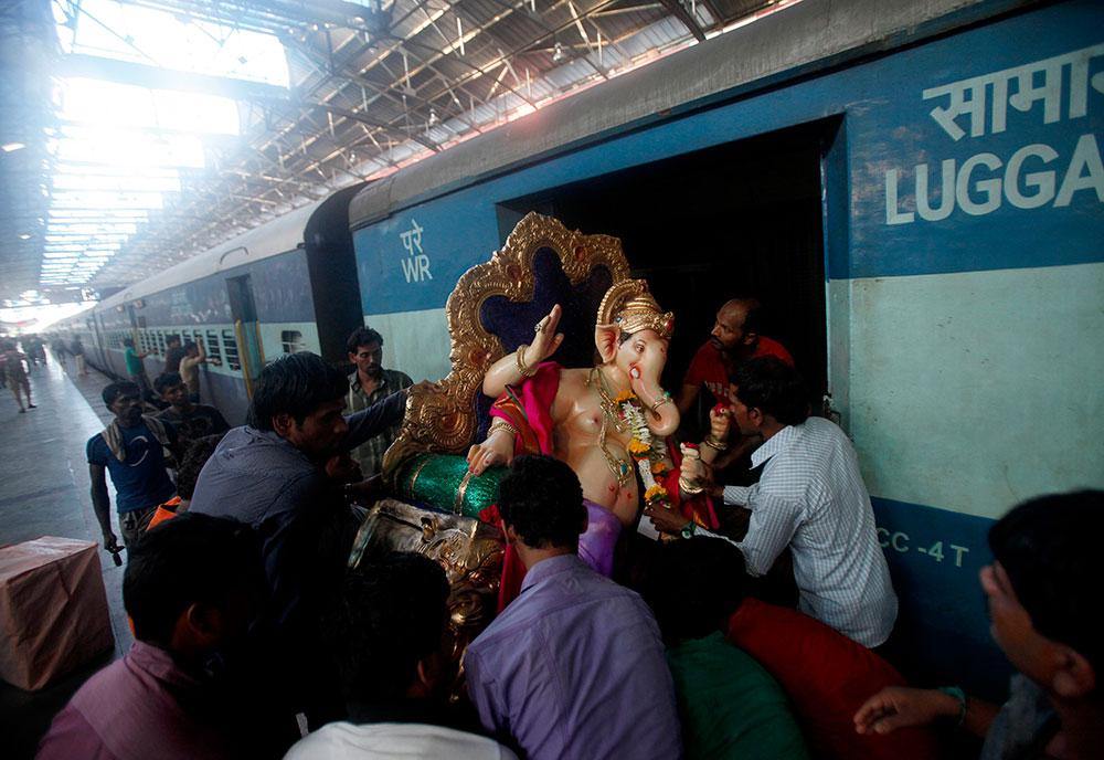 मुंबई में गणपति की प्रतिमा को पैसेंजर ट्रेन से ले जाते हुए श्रद्धालु।