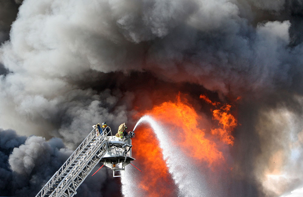 न्यूर्जी में वाटसन फूट डिस्ट्रीब्यूशन प्लांट में लगी आग पर काबू पाने की कोशिश में दमकलकर्मी।