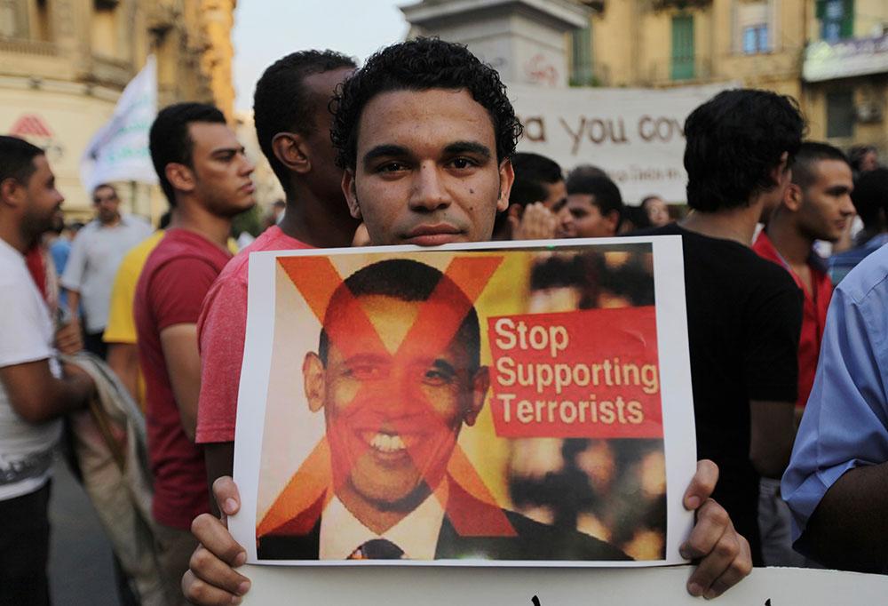 मिस्र के काहिरा में सीरिया पर यूएस हमले की संभावना के खिलाफ प्रदर्शन करते लोग।