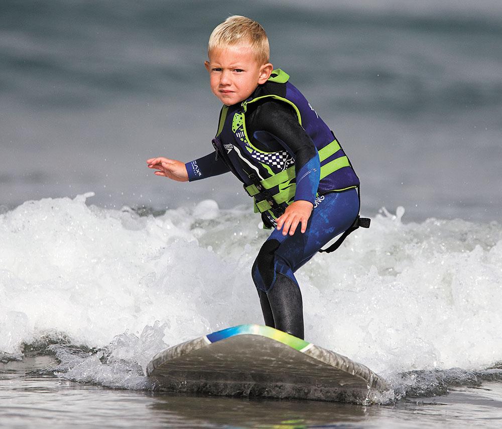 3 साल का बच्चा कैलिफ में समंदर में सर्फिंग करते हुए।