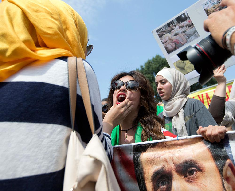 सीरिया में अमेरिकी रुख के खिलाफ विरोध प्रदर्शन करते लोग।