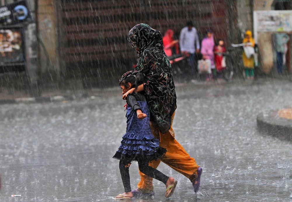 श्रीनगर में जोरदार बारिश हुई और इससे बचने की कोशिश करती एक महिला अपने बच्चे के साथ।