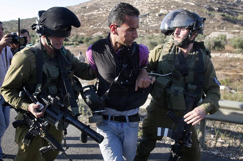 प्रदर्शन के दौरान फिलीस्तीन के एक व्यक्ति को हिरासत में लेते हुए इजरायली सैनिक।