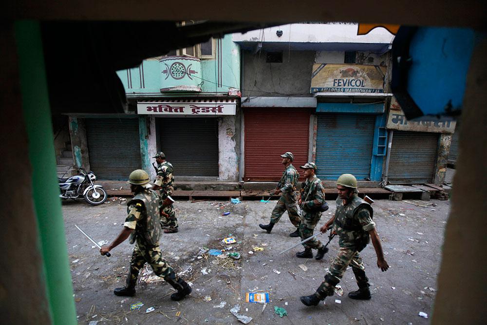 उत्तर प्रदेश के मुजफ्फरनगर में दो संप्रदायों के बीच भड़की हिंसा के बाद मार्च करती सेना।