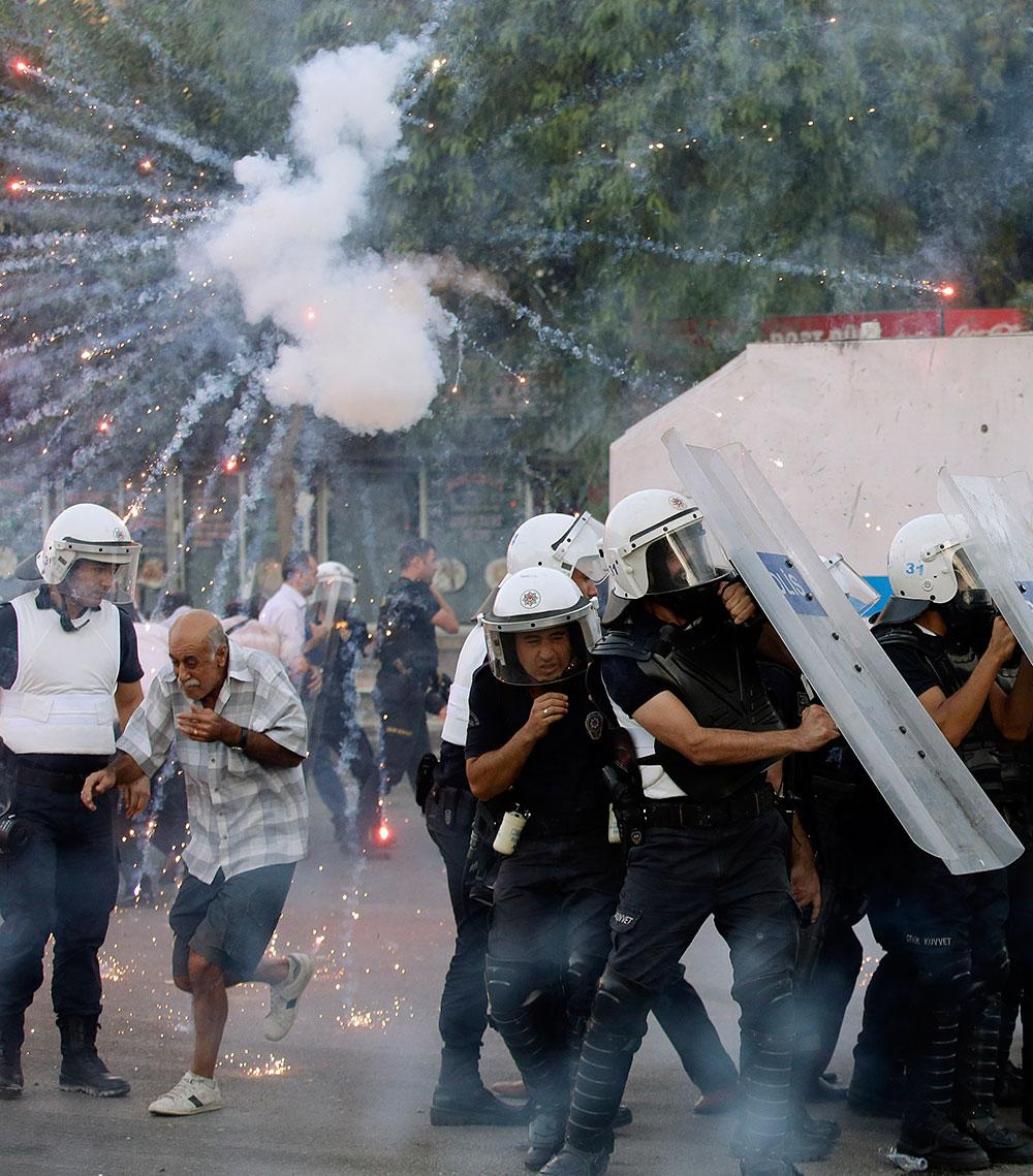 टर्की में प्रदर्शनकारियों द्वारा फेंके गए फायरवर्क्स बचाव करते पुलिसकर्मी।