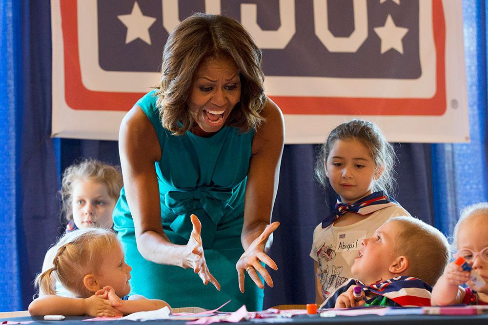 अमेरिका की प्रथम महिला मिशेल ओबामा फोर्ट बेलव्यार स्थित यूएसओ वॉरियर और फैमिली सेंटर में बच्चों के आर्ट वर्क को देखकर उनकी तारीफ करती हुईं।