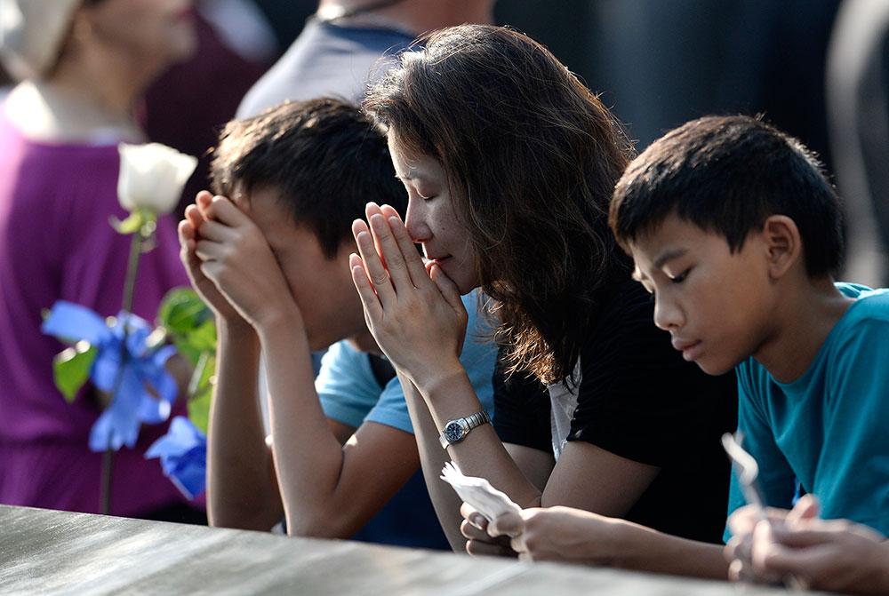 न्यूयार्क में 9/11 हमले की 12वीं बरसी पर लोग प्रार्थना करते हुए।
