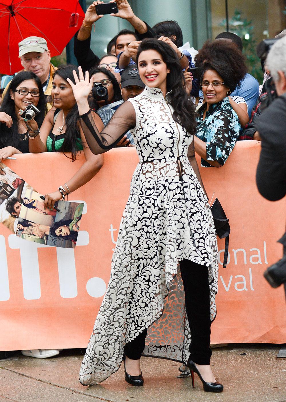 टोरंटो फिल्म फेस्टिवल 2013 के दौरान 'ए रेंडम देसी रोमांस' के प्रीमियर के मौके पर पहुंची भारतीय अभिनेत्री परिणीति चोपड़ा फैंस का हाथ हिलाकर अभिवादन करते हुए।