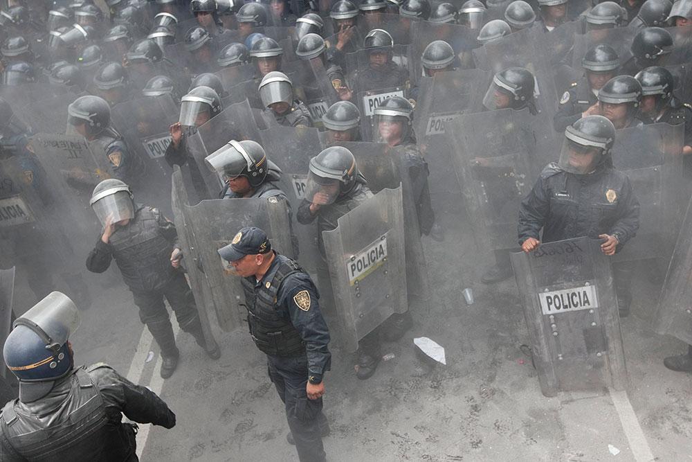 मेक्सिको सिटी में दंगा निरोधी पुलिसकर्मी हालात पर काबू पाने की कोशिश करती हुई।