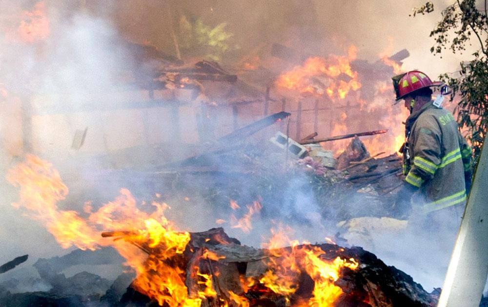 स्टेमफोर्ड में वेब्स हिल रोड पर घर में लगी आग पर काबू पाने की कोशिश करते हुए।