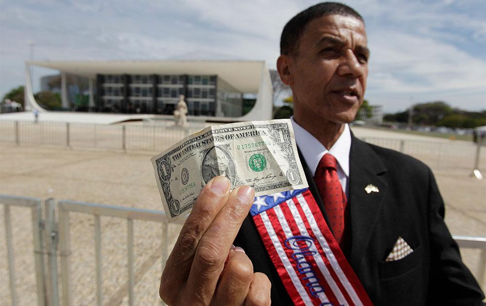 ब्राजील सुप्रीम कोर्ट के बाहर एक व्यक्ति अमेरिकी मुद्रा डॉलर का विरोध करते हुए।