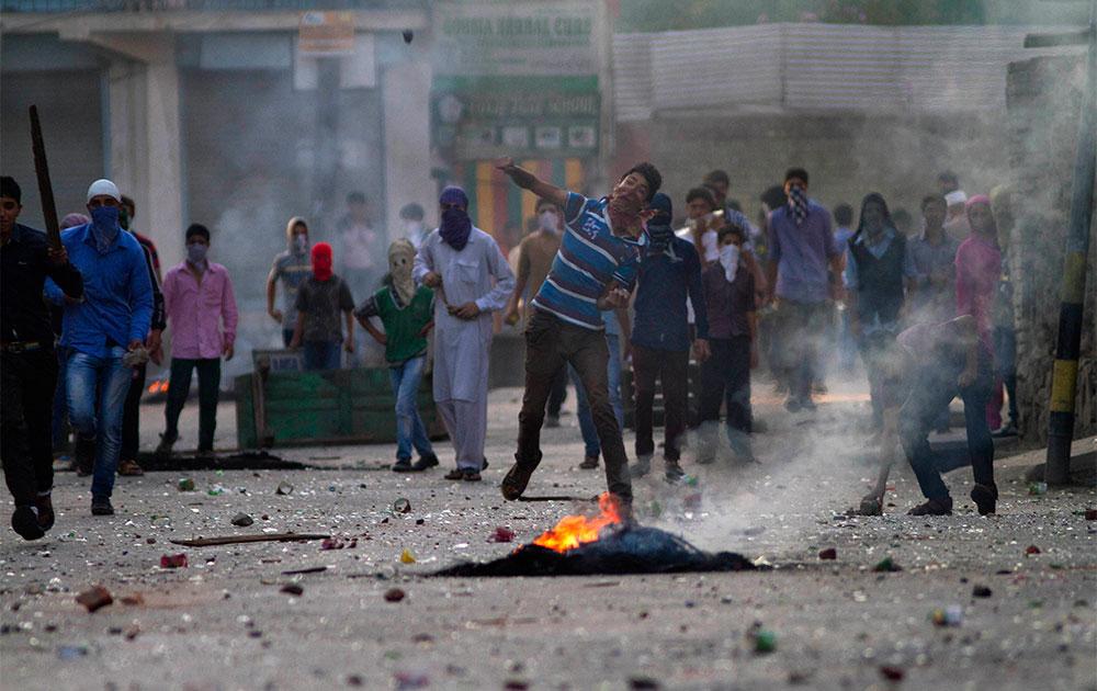 श्रीनगर में सुरक्षा बलों पर पथराव करते प्रदर्शनकारी।