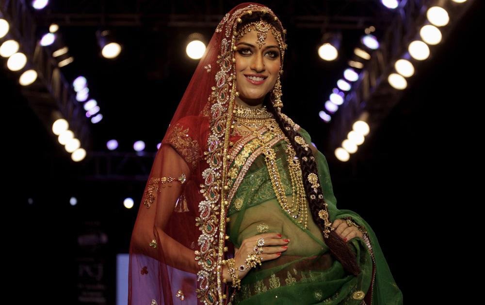 अहमदाबाद में इंडिया ज्वैलरी एंड फैशन वीक के दौरान डिजायन कपड़ों को पेश करती एक मॉडल।