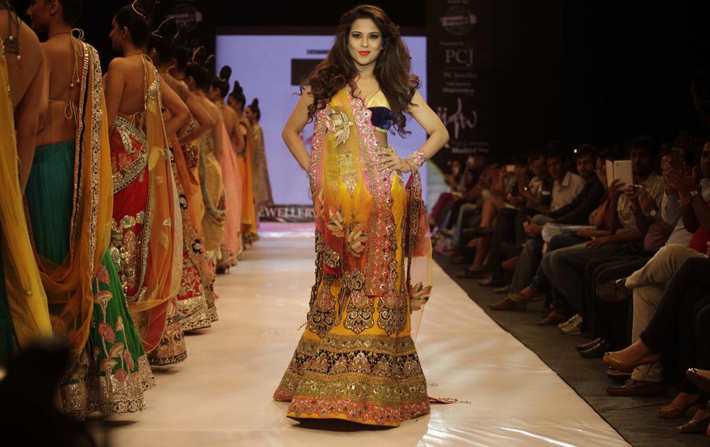 अहमदाबाद में इंडिया ज्वैलरी एंड फैशन वीक के दौरान डिजायन कपड़ों को पेश करतीं मॉडल।