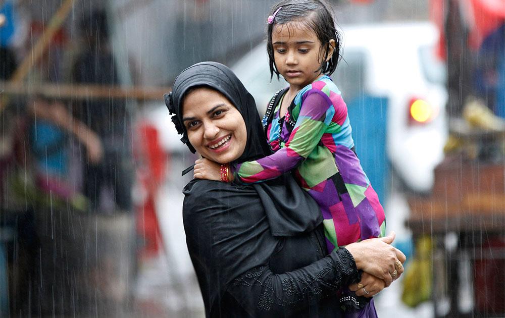 इलाहाबाद में बारिश के दौरान एक महिला अपने बच्चे के साथ।