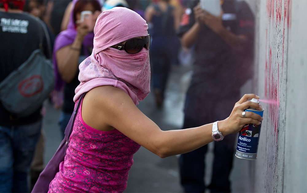 मैक्सिको सिटी में स्प्रे करता एक प्रदर्शनकारी।