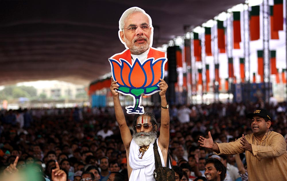 नई दिल्ली में नरेंद्र मोदी की रैली के दौरान उनके पोस्टर के साथ उनका समर्थक।