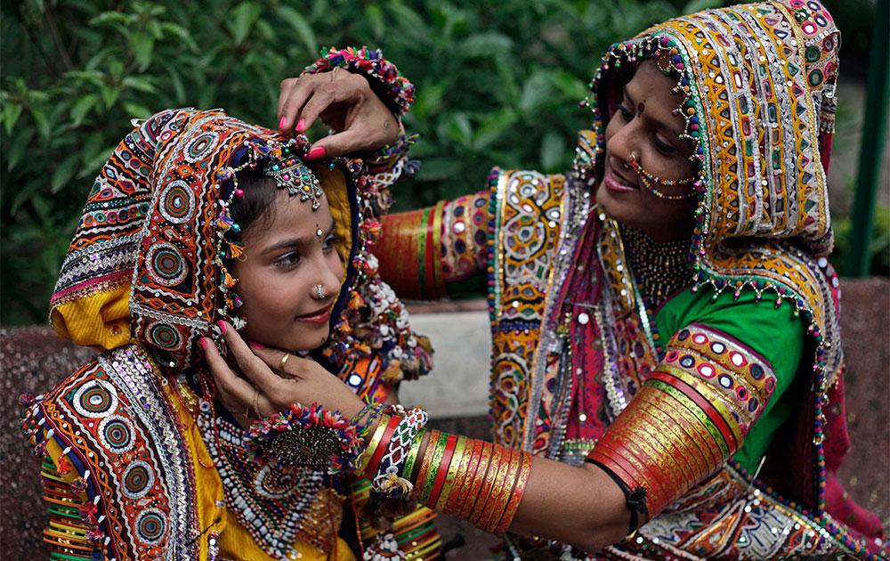 अहमदाबाद में गरबा नृत्य के लिए एक बच्ची को तैयार करती महिला।