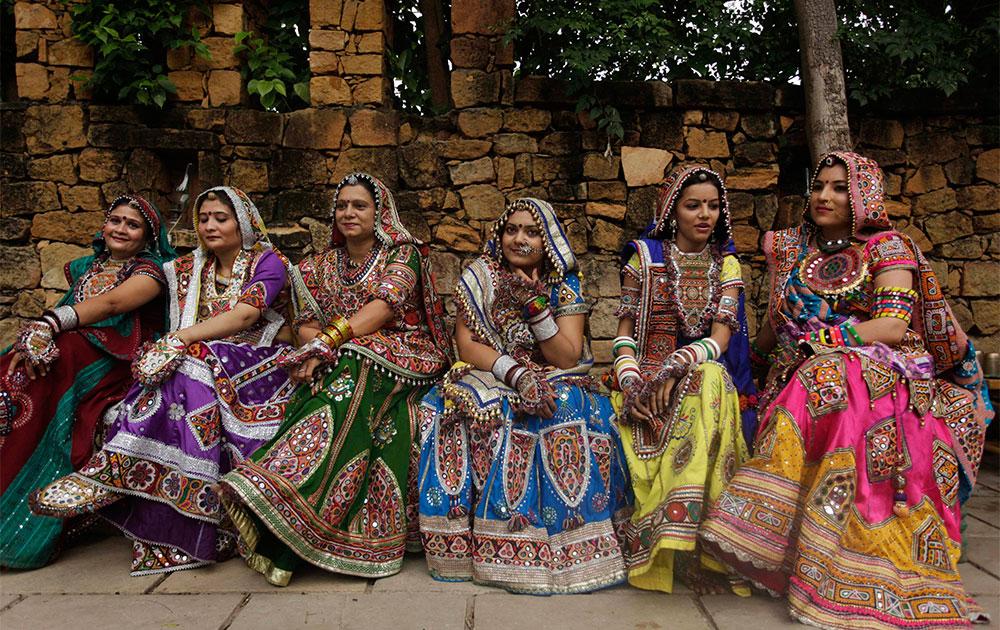 अहमदाबाद में गरबा नृत्य के लिए तैयार बैठीं महिलाएं।
