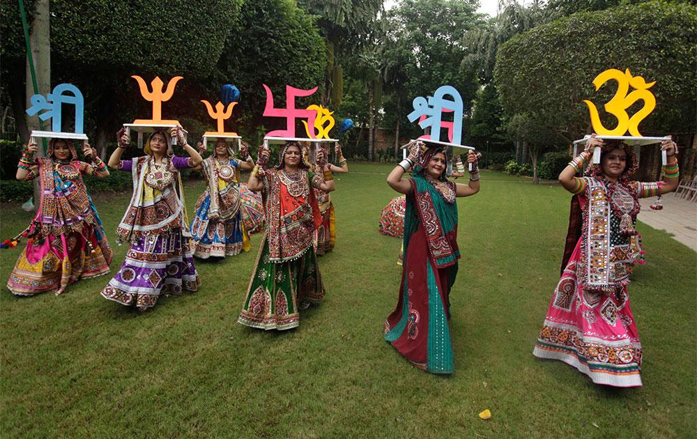 अहमदाबाद में गरबा नृत्य के लिए शुभ हिंदू प्रतीकों को सिर पर रख कर ले जातीं महिलाएं।