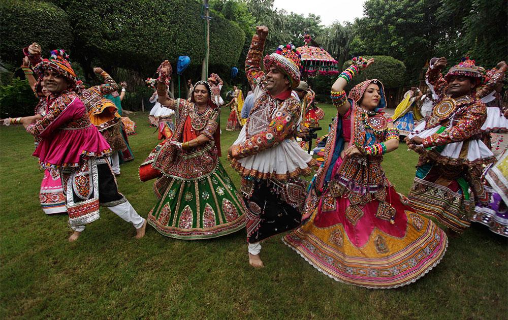 अहमदाबाद में पारंपरिक गरबा नृत्य का अभ्यास करते महिलाएं एवं पुरुष।
