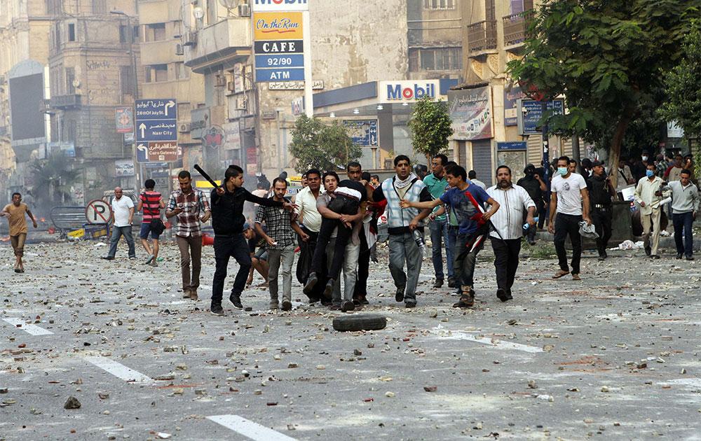 काहिरा में अपदस्थ राष्ट्रपति मोरसी के एक समर्थक को हिरासत में लेते सुरक्षा बल।