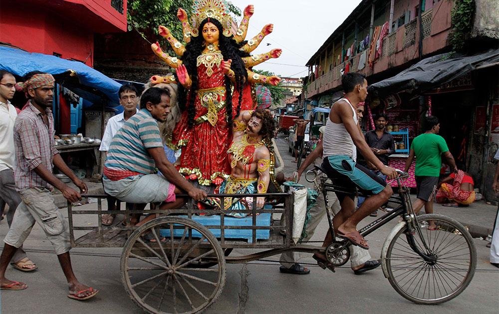 कोलकाता में माता दुर्गा की मूर्ति रिक्शे पर ले जाते लोग।