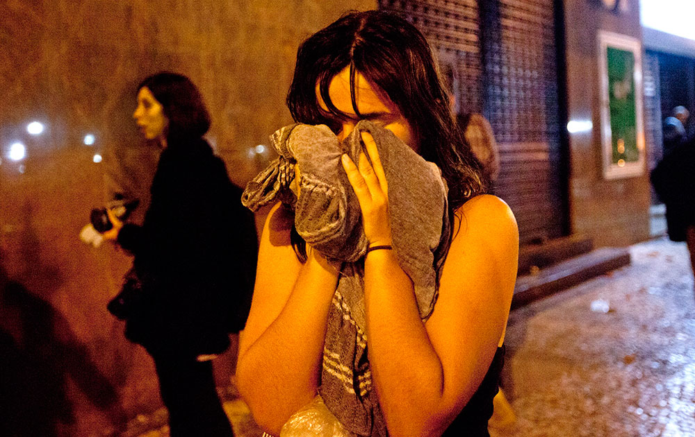 रियो डि जनेरियो में प्रदर्शन के दौरान आंसू गैस से बचने की कोशिश करती एक महिला।