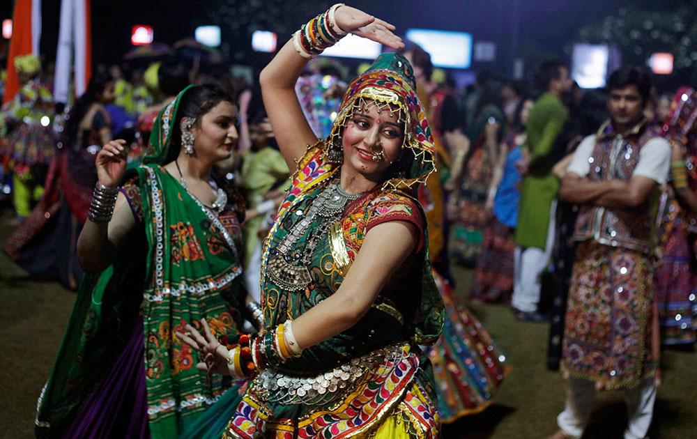 अहमदाबाद में नवरात्र फेस्टिवल के दौरान पारंपरिक वेशभूषा में गरबा नृत्य करती हुईं महिलाएं।