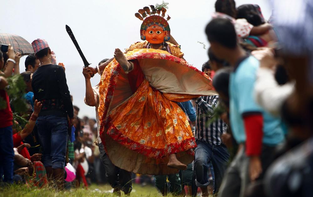 नेपाल के ललितपुर में शिकाली फेस्टिवल के दौरान देवी के रूप में नृत्य करती एक श्रद्धालु।
