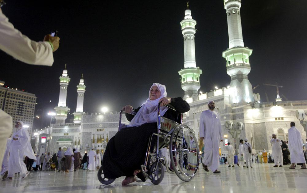 सऊदी अरब के मक्का में व्हील चेयर पर हज के लिए जाती एक महिला।