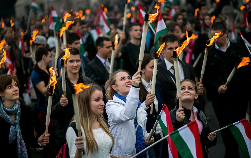 बुडापेस्ट की सड़कों पर नेशनल फ्लैग के साथ मार्च करते हंगरी के छात्र।