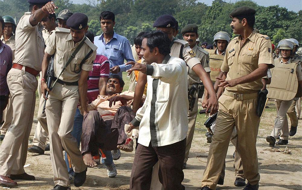 पटना के गांधी मैदान में नरेंद्र मोदी की हुंकार रैली के दौरान सीरियल बम ब्लास्ट में घायल व्यक्ति को इलाज के लिए ले जाती पुलिस।