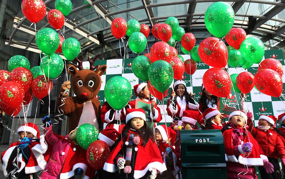 सियोल में क्रिसमस से पहले चंदे जुटाने के लिए सांता के रूप में कई बच्चे।