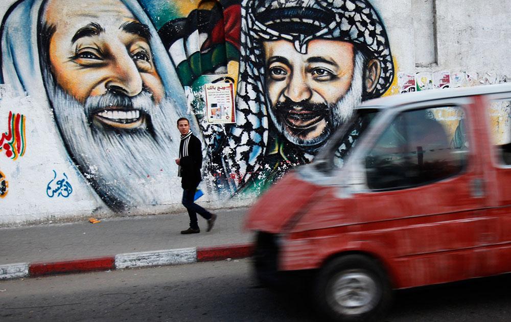 गाजा सिटी में फिलिस्तीनियों के दिवंगत नेता यासर अराफा, और हमास नेता शेख अहमद यासिन की तस्वीर के पास से गुजरता एक फिलिस्तीनी।