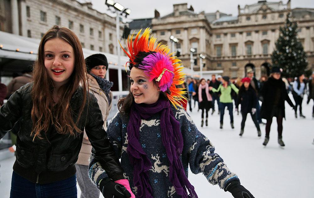 सेंट्रल लंदन के समरसेट हाउस में बर्फ पर स्केटिंग का आनंद लेते बच्चे।