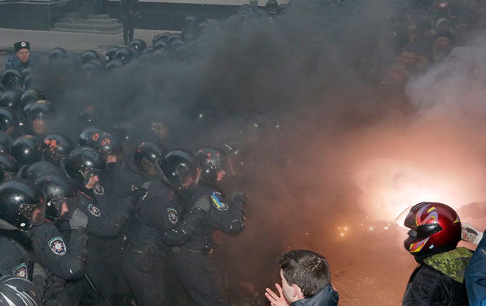 यूक्रेन में राष्ट्रपति के ऑफिस के बाहर प्रदर्शनकारियों पर अश्रुगैस छोड़ते पुलिस।