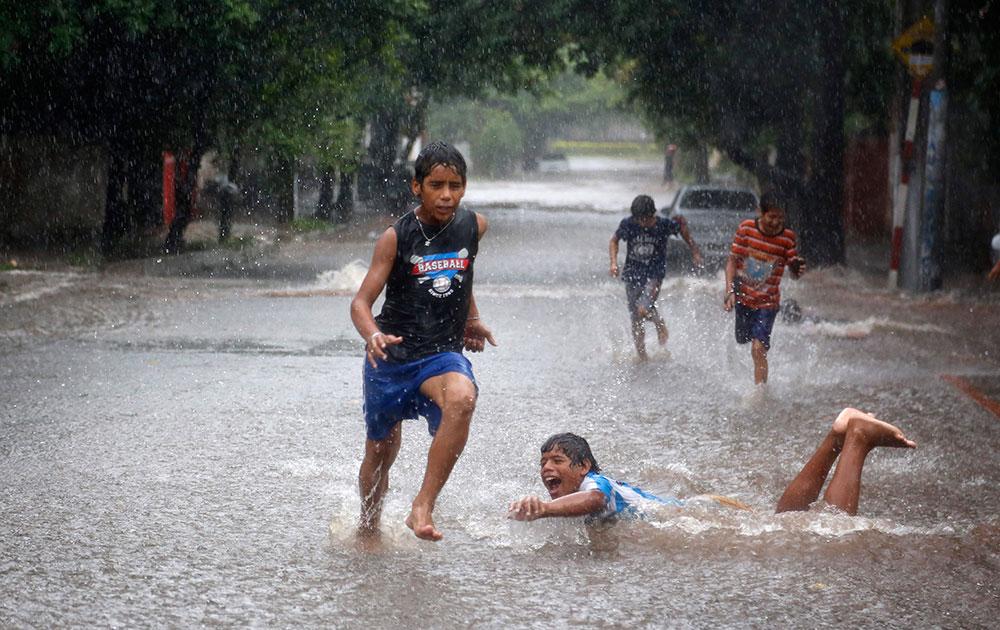 पराग्वे के ऑक्सियन में भारी बारिश से हुए जमा पानी में खेलते बच्चे।