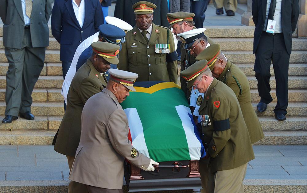 दक्षिण अफ्रीका के पूर्व राष्ट्रपति नेल्सन मंडेला के पार्थिव शरीर वाले कॉफिन को राष्ट्रीय ध्वज में लपेटकर ले जाते सुरक्षाकर्मी।