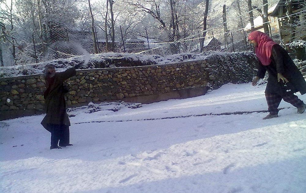 अनंतनाग में बर्फबारी का आनंद उठाती हुईं कश्मीरी लड़कियां।